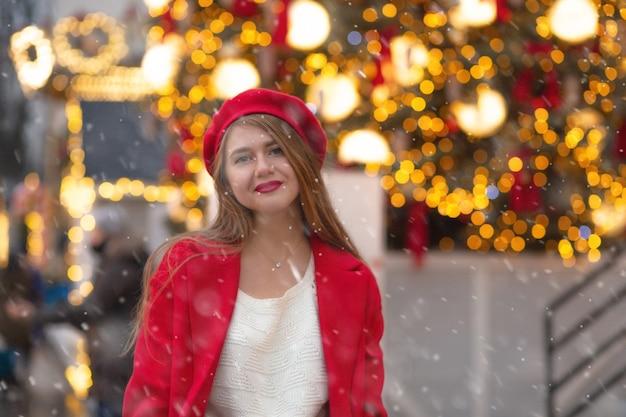 Glimlachende jonge vrouw in rode jas wandelen op de straatmarkt tijdens de sneeuwval. lege ruimte