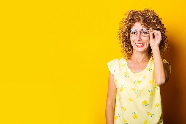 Glimlachende jonge vrouw in ronde transparante bril op een gele achtergrond.