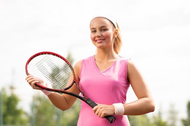 Glimlachende jonge vrouw in roze jurk klaar om te tennissen op de buitenbaan