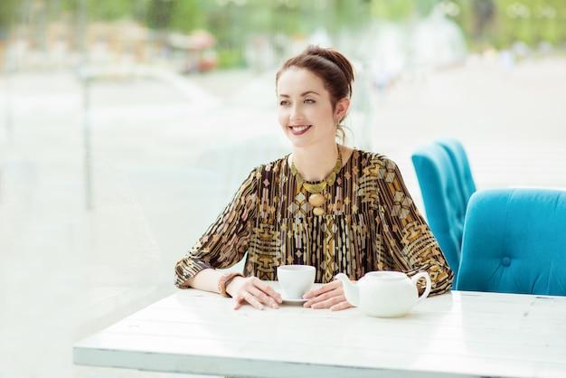 Glimlachende jonge vrouw in stadscafé met kop hete thee en theepot