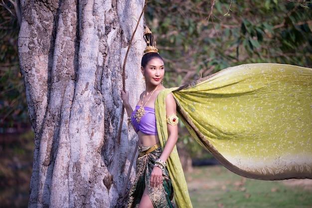 Glimlachende jonge vrouw in traditionele kleding die zich tegen boomboomstam bevinden