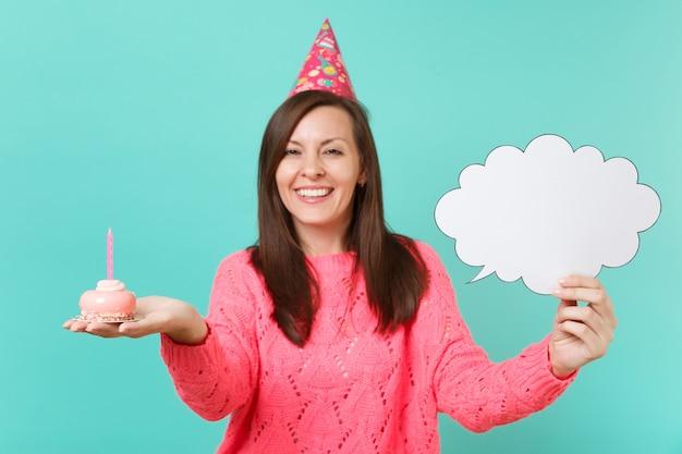 Glimlachende jonge vrouw in verjaardagshoed in hand taart met kaars leeg leeg say cloud tekstballon voor promotionele inhoud geïsoleerd op blauwe achtergrond. mensen levensstijl concept. bespotten kopie ruimte.