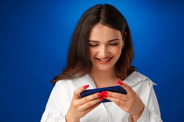 Glimlachende jonge vrouw in wit overhemd die haar smartphone tegen blauwe achtergrond gebruikt
