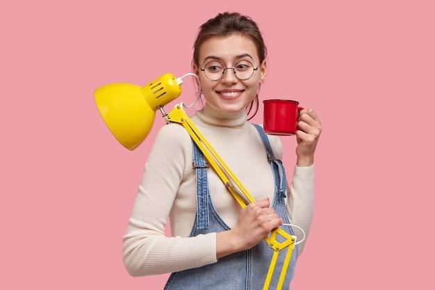Glimlachende jonge vrouw journalist werkt vanuit huis, draagt gele tafellamp en mok drank, kijkt vrolijk, heeft koffiepauze