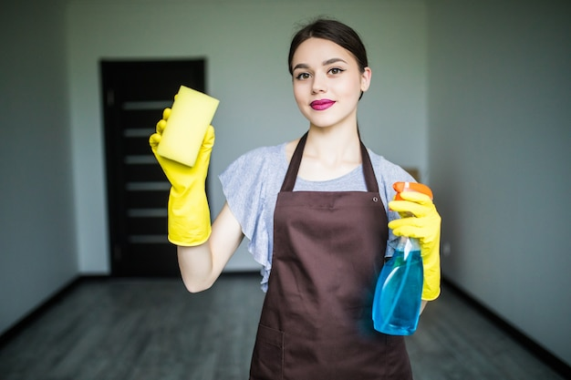 Glimlachende jonge vrouw maakt het raam schoon met rag