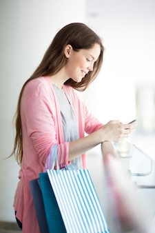 Glimlachende jonge vrouw met behulp van smartphone in het winkelcentrum