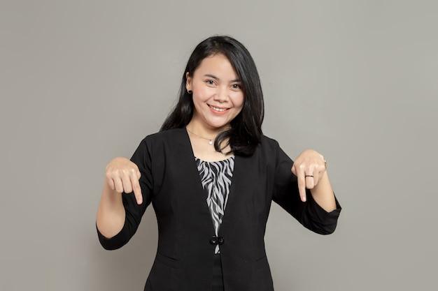 Glimlachende jonge vrouw met beide handen naar beneden gericht