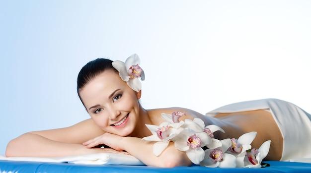 Glimlachende jonge vrouw met bloemen die in de kuuroordsalon rusten vóór massage