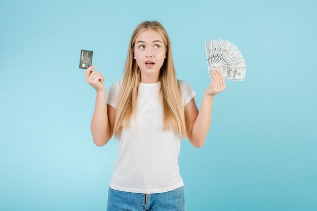 Glimlachende jonge vrouw met creditcard en dollarsgeld in haar die handen over blauw wordt geïsoleerd