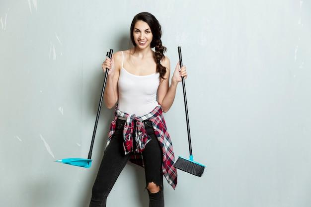 Glimlachende jonge vrouw met een borstel en schep staat tegen de achtergrond van een grijs geschilderde muur. reiniging, constructie en reparatie.