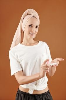 Glimlachende jonge vrouw met een handdoek die micellair water op een wattenschijfje sproeit om make-up af te vegen