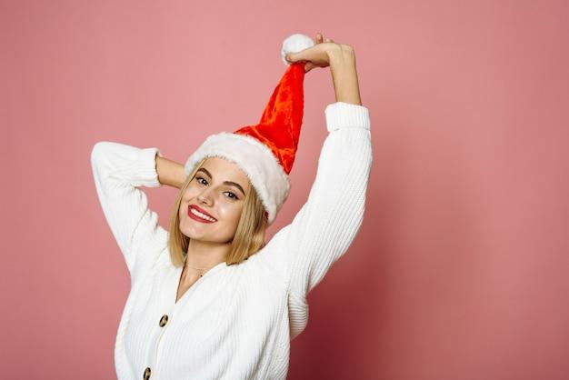 Glimlachende jonge vrouw met een kerstmuts achter een pompon op een roze achtergrond gelach
