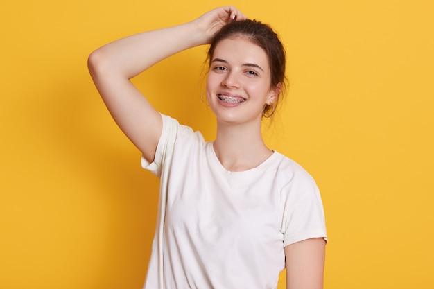 Glimlachende jonge vrouw met gelukkige gezichtsuitdrukking, die witte t-shirt draagt