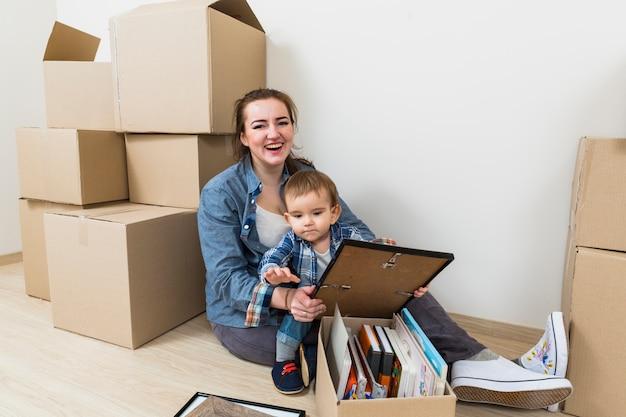 Glimlachende jonge vrouw met haar zoon zit in haar nieuwe huis met kartonnen dozen