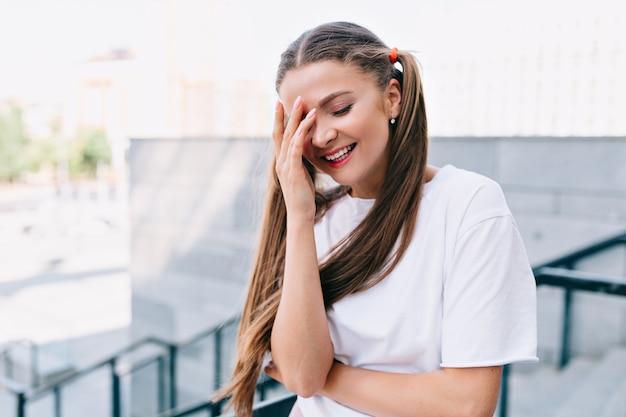 Glimlachende jonge vrouw met hand op het gezicht en glimlacht met gesloten ogen