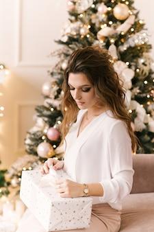 Glimlachende jonge vrouw met kerstcadeaudoos in de buurt van kerstboom