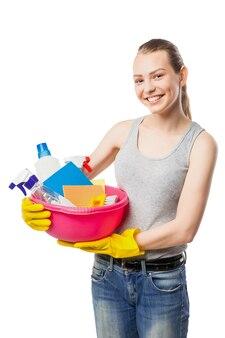 Glimlachende jonge vrouw met kom reinigingsmiddelen en doekjes, close-up, huisvrouw, geïsoleerd op wit