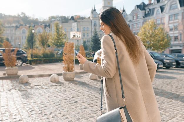 Glimlachende jonge vrouw met mobiele telefoon het lopen