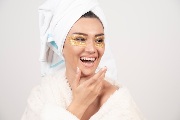 Glimlachende jonge vrouw met patches onder de ogen in badjas.