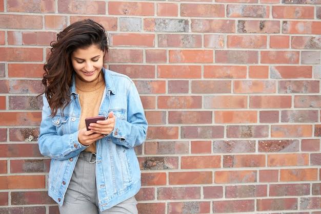 Glimlachende jonge vrouw met slimme telefoon in de stad