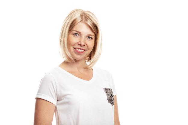 Glimlachende jonge vrouw met sproeten op haar gezicht. geã¯soleerd op een witte achtergrond.