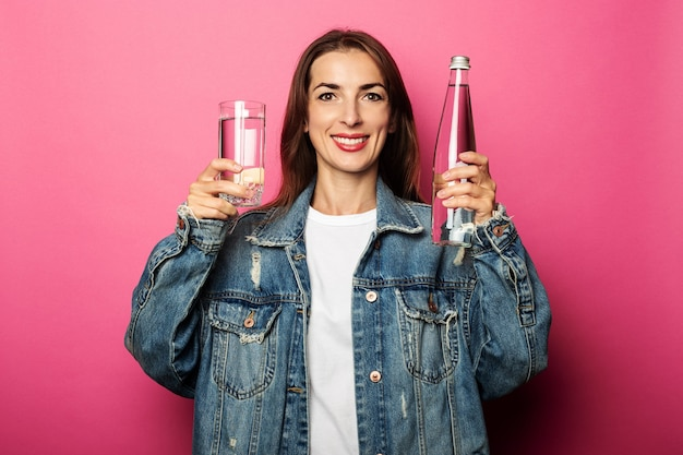 Glimlachende jonge vrouw met waterfles en glas water