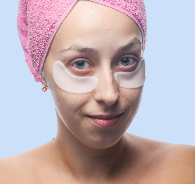 Glimlachende jonge vrouw met witte vlekken onder de ogen en een roze handdoek op haar hoofd dat op blauw wordt geïsoleerd. closeup portret. huidverzorging