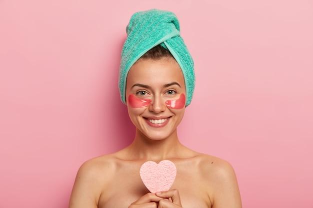 Glimlachende jonge vrouw met zachte glimlach, witte tanden, draagt een gewikkelde handdoek over het hoofd, houdt een hartvormige cosmetische spons vast, voedt de huid, ziet er jong en energiek uit, toont blote schouders, staat binnen
