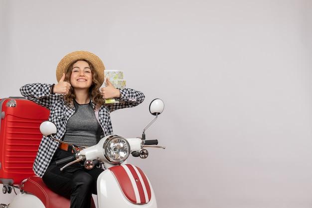 Glimlachende jonge vrouw op bromfiets die kaart vasthoudt en duimen omhoog tekent op grijs