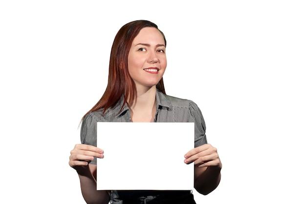 Glimlachende jonge vrouw op een witte achtergrond heeft een witte lege banner met copyspace