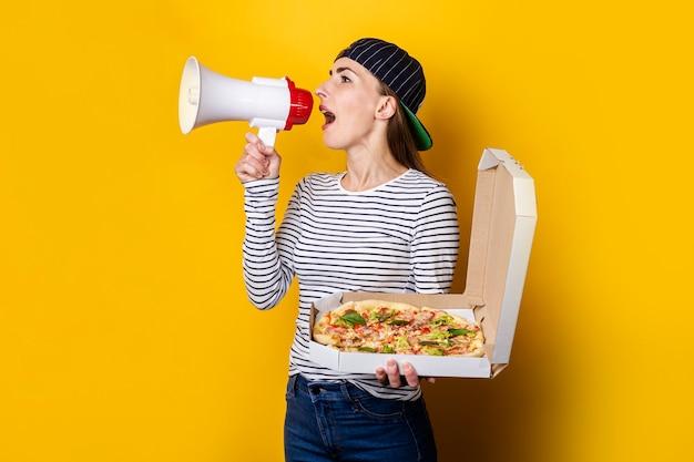 Glimlachende jonge vrouw pizzabezorger die in een megafoon schreeuwt terwijl hij pizza op geel houdt