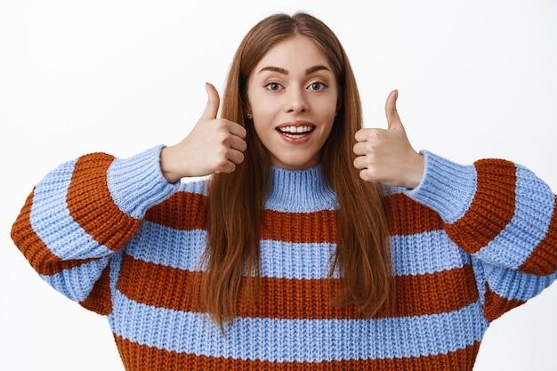 Glimlachende jonge vrouw prijst goede keuze, toont duimen omhoog gebaar, keurt goed en leuk, zeg ja, steunplan, staande over witte muur