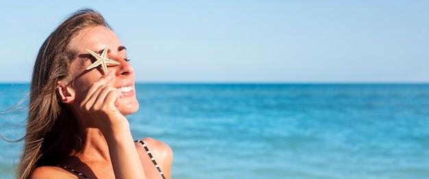 Glimlachende jonge vrouw sluit haar oogzeester op het strand. banier.
