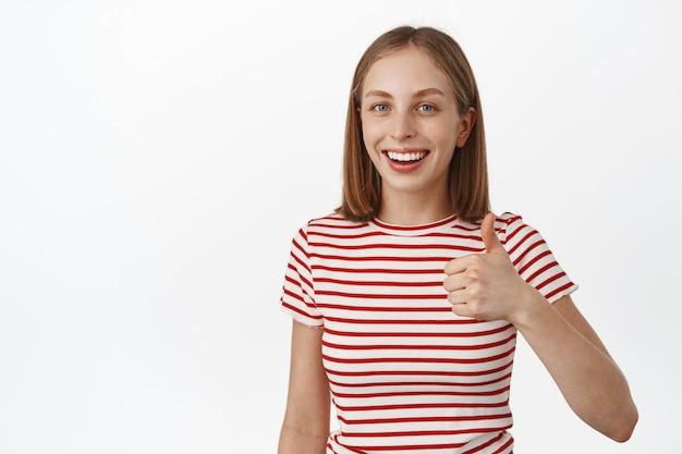 Glimlachende jonge vrouw, student duim omhoog in goedkeuring, kijk tevreden, product aanbevelen, leuk vinden en mee eens, positieve feedback, staande tegen de witte muur.