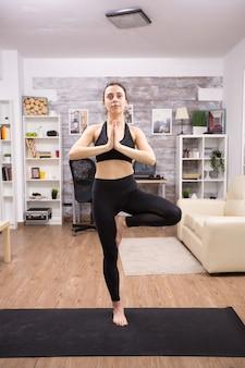 Glimlachende jonge vrouw tijdens het doen van boomyoga pose met zwarte sportkleding in huis.