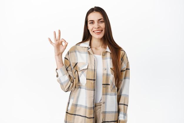 Glimlachende jonge vrouw toont goed teken en knikt goedkeurend, ziet er tevreden uit, tevreden met goede kwaliteit, prijs mooi werk, uitstekende keuze, staat over witte muur