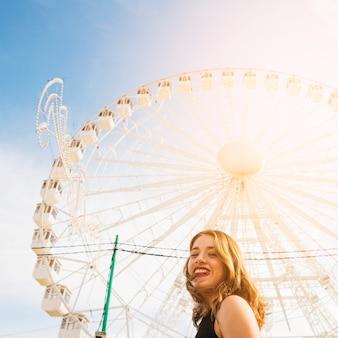 Glimlachende jonge vrouw voor wit reuzeferriswiel tegen blauwe hemel