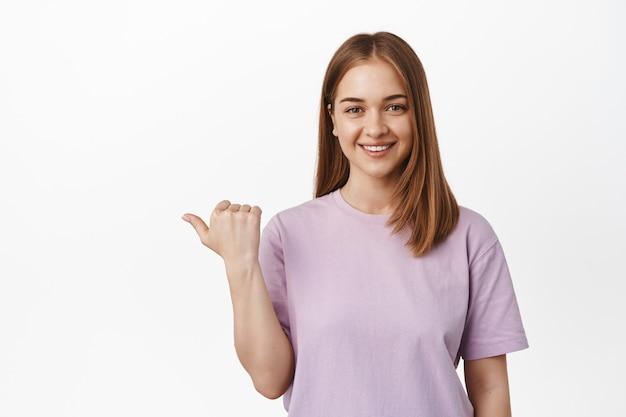 Glimlachende jonge vrouw, vrouwelijke assistent die duim naar links wijst en er vriendelijk uitziet, richting toont, logobanner op lege ruimte opzij, witte muur