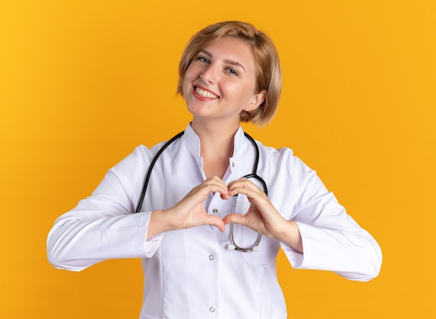 Glimlachende jonge vrouwelijke arts die een medisch gewaad draagt met een stethoscoop die een hartgebaar toont dat op een oranje achtergrond wordt geïsoleerd