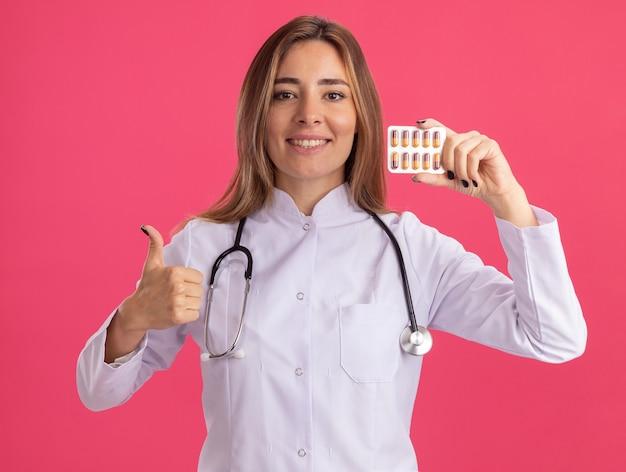 Glimlachende jonge vrouwelijke arts die een medisch gewaad draagt met een stethoscoop die pillen vasthoudt en een duim toont die op een roze muur is geïsoleerd