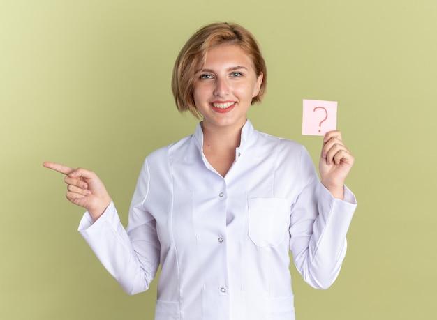 Glimlachende jonge vrouwelijke arts die een medisch gewaad draagt met een stethoscoop met een vraag op papier aan de zijkant geïsoleerd op een olijfgroene achtergrond