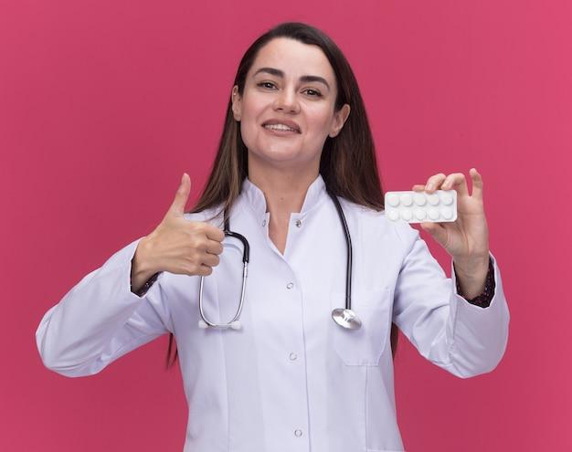 Glimlachende jonge vrouwelijke arts die een medisch gewaad met een stethoscoop draagt, houdt een pakje medicijnen vast en duimen omhoog geïsoleerd op een roze muur met kopieerruimte
