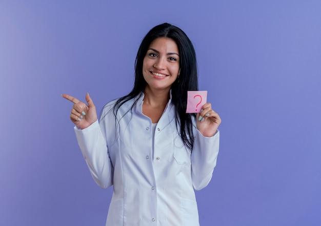 Glimlachende jonge vrouwelijke arts die het vraagteken van de medische mantelholding naar kant richt die op purpere muur met exemplaarruimte wordt geïsoleerd