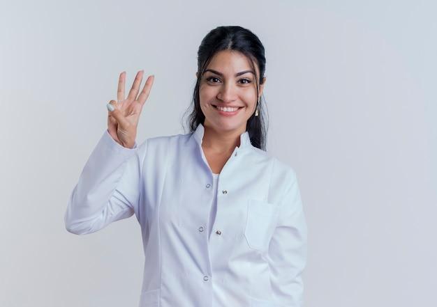 Glimlachende jonge vrouwelijke arts die medisch kleed draagt dat en drie met geïsoleerde hand kijkt toont