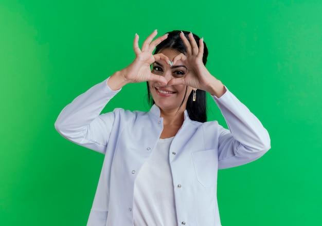 Glimlachende jonge vrouwelijke arts die medisch kleed draagt dat hartteken doet dat op groene muur wordt geïsoleerd