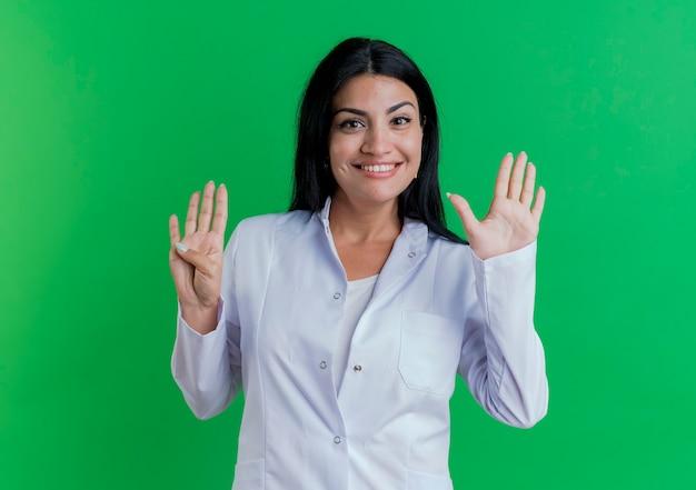 Glimlachende jonge vrouwelijke arts die medisch kleed draagt dat negen met handen toont die op groene muur met exemplaarruimte worden geïsoleerd