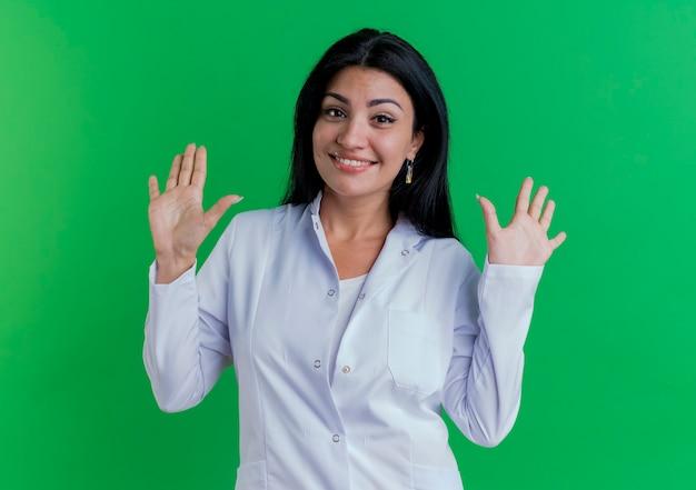 Glimlachende jonge vrouwelijke arts die medisch kleed draagt dat toont tien met handen kijkt