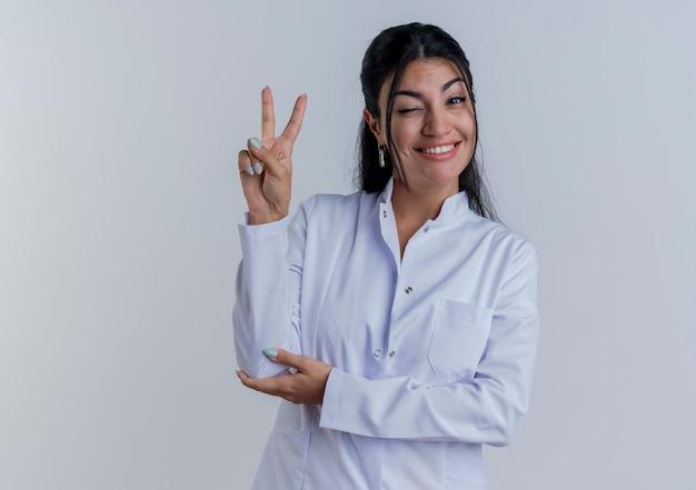 Glimlachende jonge vrouwelijke arts die medisch kleed draagt dat vredesteken doet die hand op elleboog zetten die op witte muur met exemplaarruimte wordt geïsoleerd