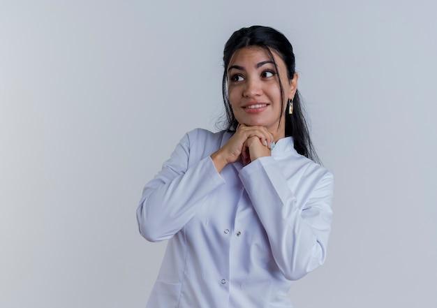 Glimlachende jonge vrouwelijke arts die medisch kleed draagt die kant bekijkt die handen onder geïsoleerde kin houdt