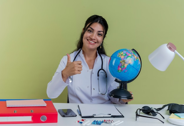 Glimlachende jonge vrouwelijke arts die medische gewaad en stethoscoopzitting bij bureau met medische hulpmiddelen draagt die bol houdt die toont geïsoleerde duim omhoog kijkt